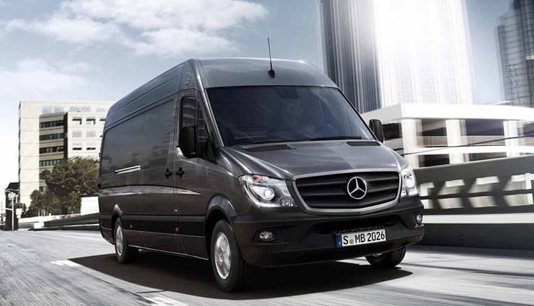 Large, black Mercedes Benz rental van driving through a city, past modern, office buildings.